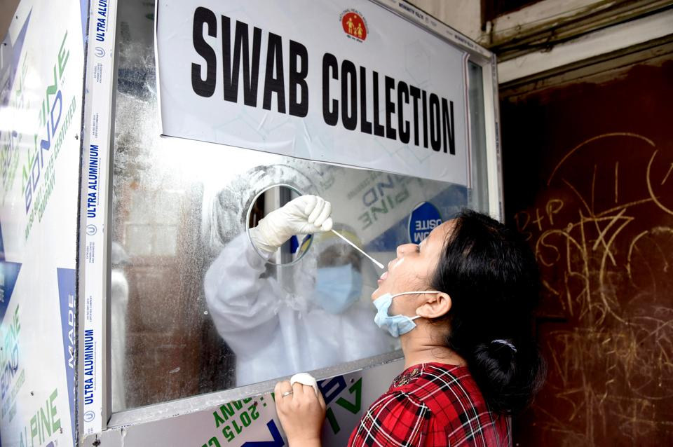 A healthcare worker collects swab sample from a woman for COVID-19 testing in Guwahati on Sunday. (Representational)
