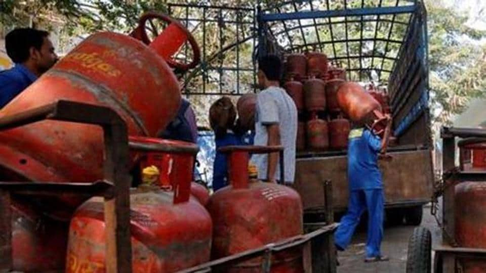 Workers load liquefied petroleum gas (LPG) cooking cylinders onto a supply truck outside a distribution centre.