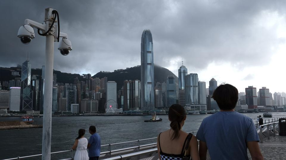 Pedestrians walk past a pair of security cameras along the Tsim Sha Tsui waterfront as buildings stand across Victoria Harbor in Hong Kong, China, on Tuesday, July 7, 2020.