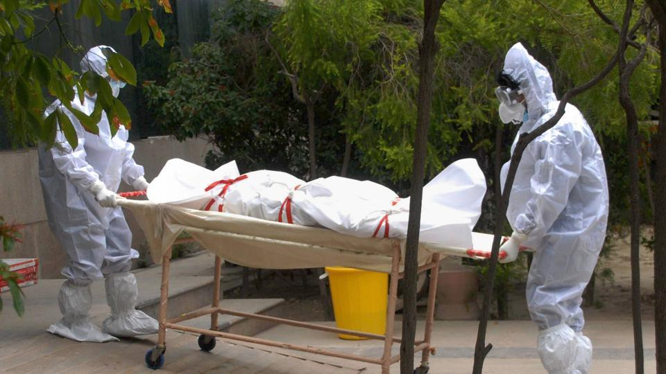 Medics wearing PPE kits carry the body of a person who died of COVID-19 at a district hospital, in Noida.