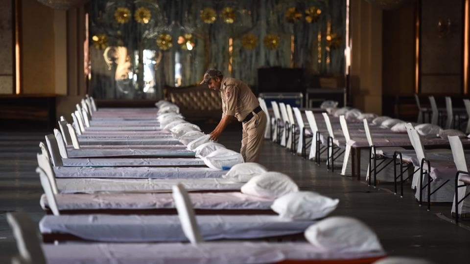 A home guard arranges beds in the hall of Heritage Grand Banquet which has been requisitioned for use as a care facility for coronavirus patients in New Delhi on July 5. The World Health Organization (WHO) reported a record single-day increase of 212,326 global coronavirus cases on July 4. On July 5, India overtook Russia to become the third worst-hit country.  (Sanchit Khanna / HT Photo)