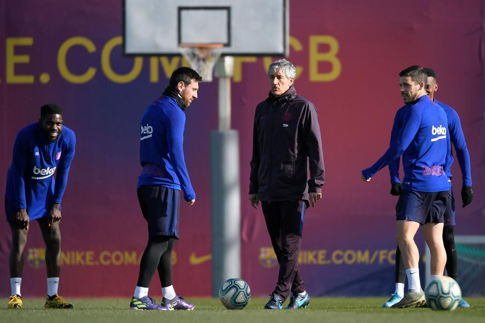 Barcelona's new coach, Spaniard Quique Setien (3L), talks with Barcelona's Argentine forward Lionel Messi (2L) during a training session at the Joan Gamper Sports City training ground in Sant Joan Despi on January 18, 2020. (Photo by LLUIS GENE / AFP)