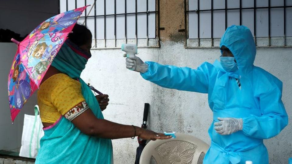A healthcare worker checks the temperature and pulse of a resident during a check-up camp for the coronavirus disease (Covid-19), in Mumbai on July 4, 2020.