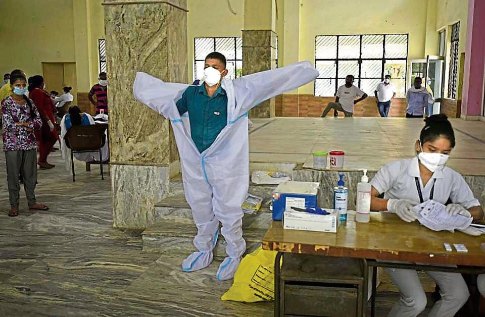 A health worker taking out his personal protective equipment at a community centre in Gurugram