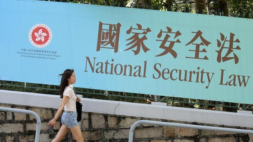 A woman walks past a promotional banner of the national security law for Hong Kong.
