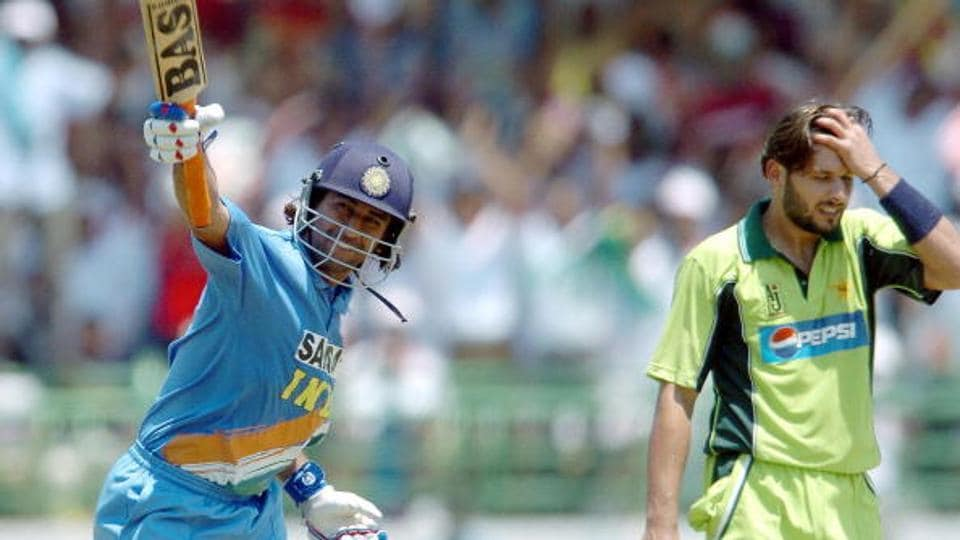 Indian cricketer Mahender Dhoni (L) celebrates after scoring a century.