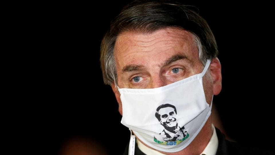 Brazil's President Jair Bolsonaro speaks with journalists while wearing a protective face mask as he arrives at Alvorada Palace, amid the coronavirus disease (COVID-19) outbreak, in Brasilia, Brazil.