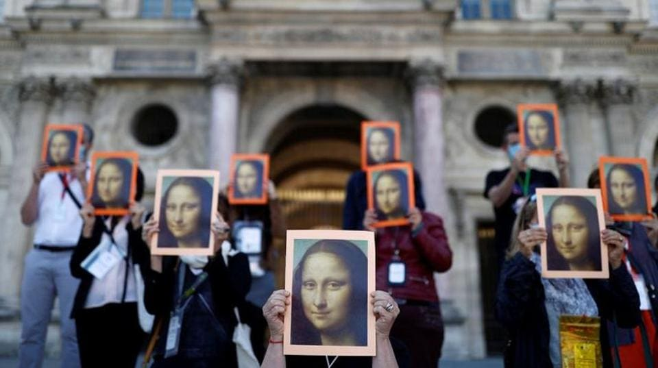 Paris tour guides hold posters depicting Mona Lisa painting by artist Leonardo da Vinci during an action at Le Louvre museum courtyard to warn on their working conditions in Paris as the museum reopens its doors to the public after almost 4-month closure due to the coronavirus disease (COVID-19) outbreak in France, July 6, 2020.