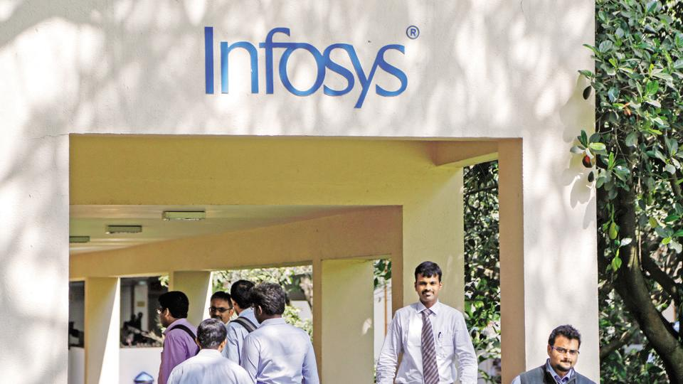 Employees walk past an Infosys logo at the campus of Infosys Ltd. at the Electronics City area in Bangalore