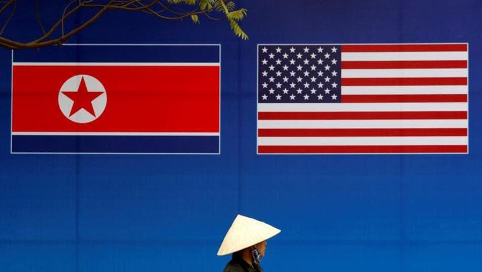 A person walks past a banner showing North Korean and U.S. flags ahead of the North Korea-U.S. summit in Hanoi, Vietnam.