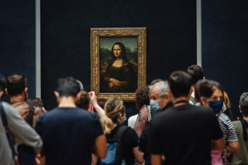 Visitors wearing protective face masks gather around The Mona Lisa in the reopened Louvre Museum in Paris, France, on Monday, July 6, 2020.