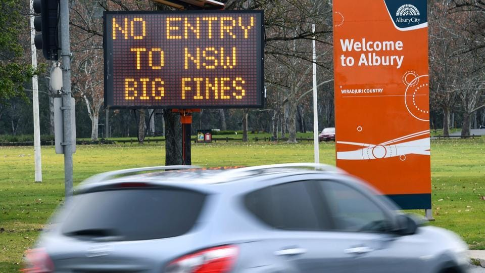 A car drives past a sign in the southern New South Wales (NSW) border city of Albury warning of fines for people entering NSW on July 7. Owing to the surge in coronavirus cases Melbourne has gone into a lockdown for the next six weeks. The entire state of Victoria will effectively be sealed off from the rest of the country. (William West / AFP)
