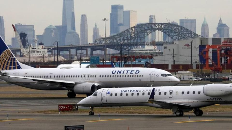 United Airlines passenger jets taxi with New York City as a backdrop, at Newark Liberty International Airport, New Jersey, US.
