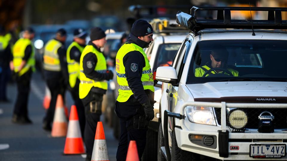 NSW police officers speak to drivers hoping to cross from the state of Victoria into New South Wales (NSW) at a border check point after the border was closed on July 8. The Victoria border with New South Wales closed on June 7, but a steady stream of cars continued to pass through police checkpoints with permits granted to travellers to cross for reasons such as work and medical treatment, reported AP. (AAP Image / Lukas Coch via REUTERS)