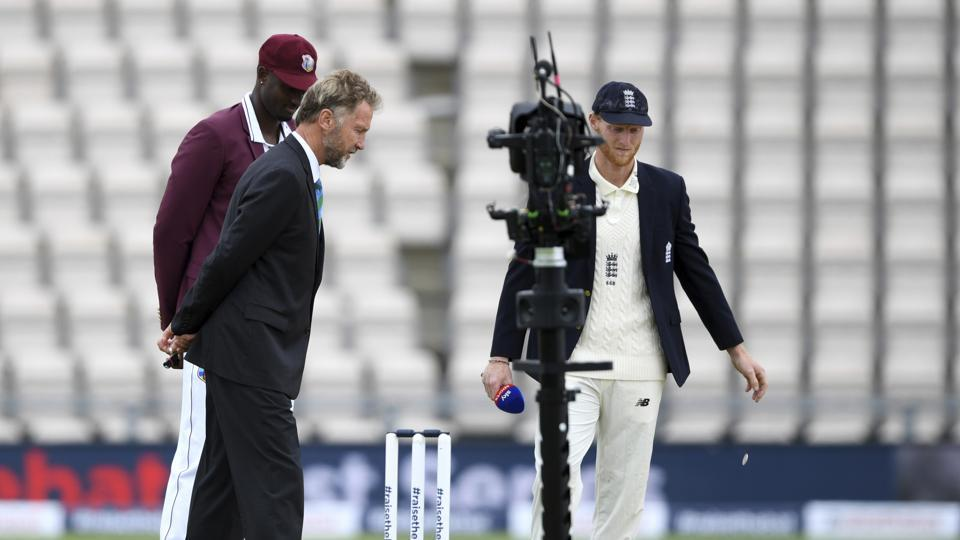 England captain Ben Stokes, right, and West Indies' captain Jason Holder, left, watch the coin before Stoke won the toss on the first day of the 1st cricket Test match between England and West Indies, at the Ageas Bowl in Southampton, England, Wednesday July 8, 2020.