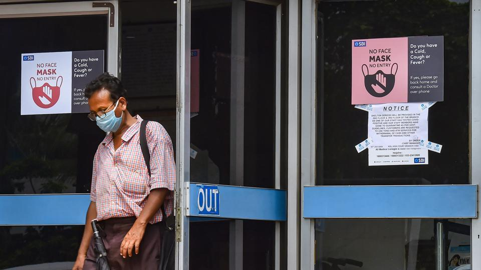 Kolkata: A customer wearing protective mask comes out of the Samriddhi Bhawan, the local head-office of the State Bank of India, in Kolkata, Tuessday, July 7, 2020.