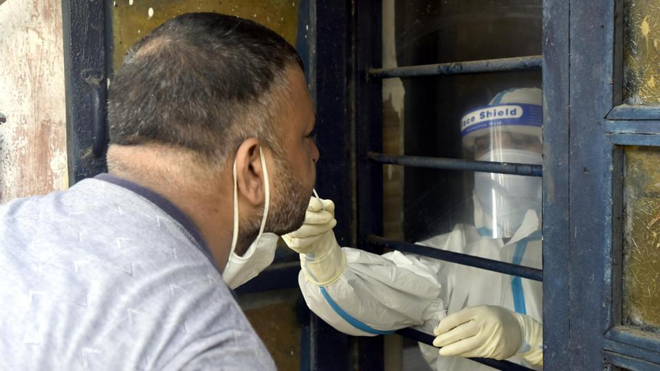 A medical worker collects a swab sample to conduct a rapid antigen test for coronavirus, at a testing centre in New Delhi's Gandhi Nagar, on Tuesday.