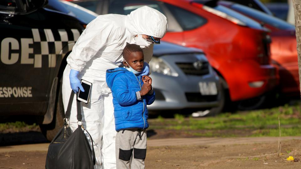 "A support worker comforts a young child after he was separated from his mother. The announcement of lockdown brought rushed evacuations on both sides of the border. ""We've had a mass evacuation of Victorians,"" Ray Bell, owner of the Twofold Bay Motor Inn in Eden, told Reuters. (Sandra Sanders / REUTERS)"