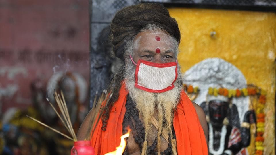 An Indian priest covers his face with a mask as a precaution against coronavirus and prays at a temple, in Prayagraj, India.