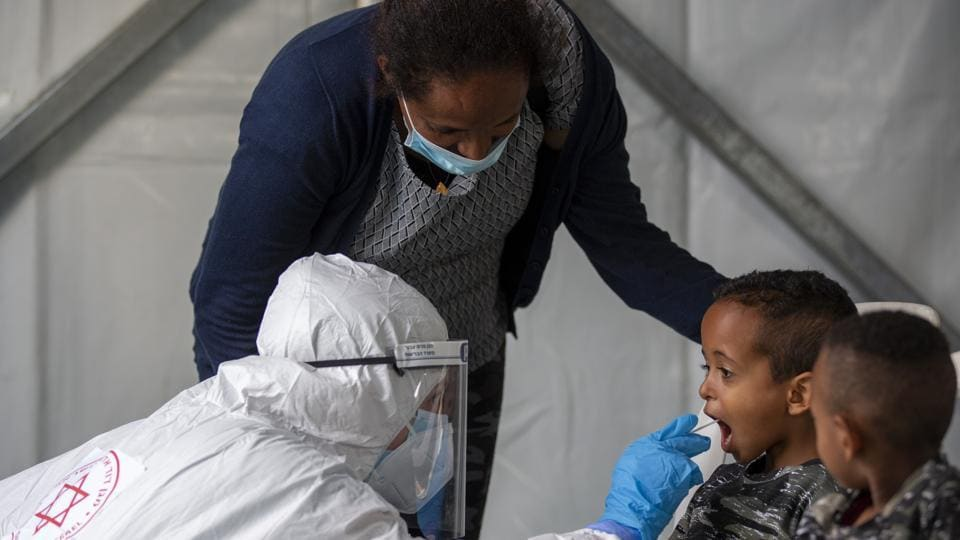 A child is tested by a healthcare worker for the coronavirus at testing center for migrants in Tel Aviv, Israel.