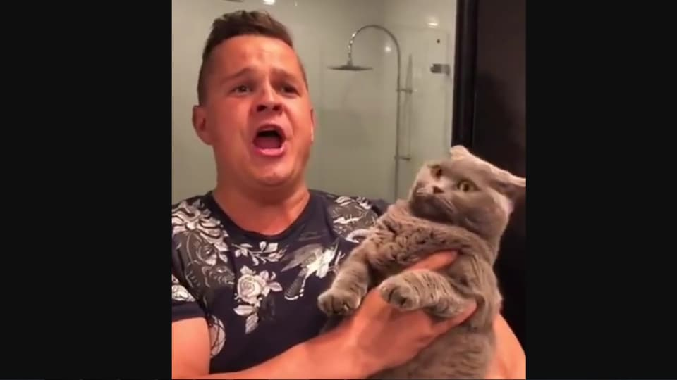 The video shows the man holding the cat while singing.