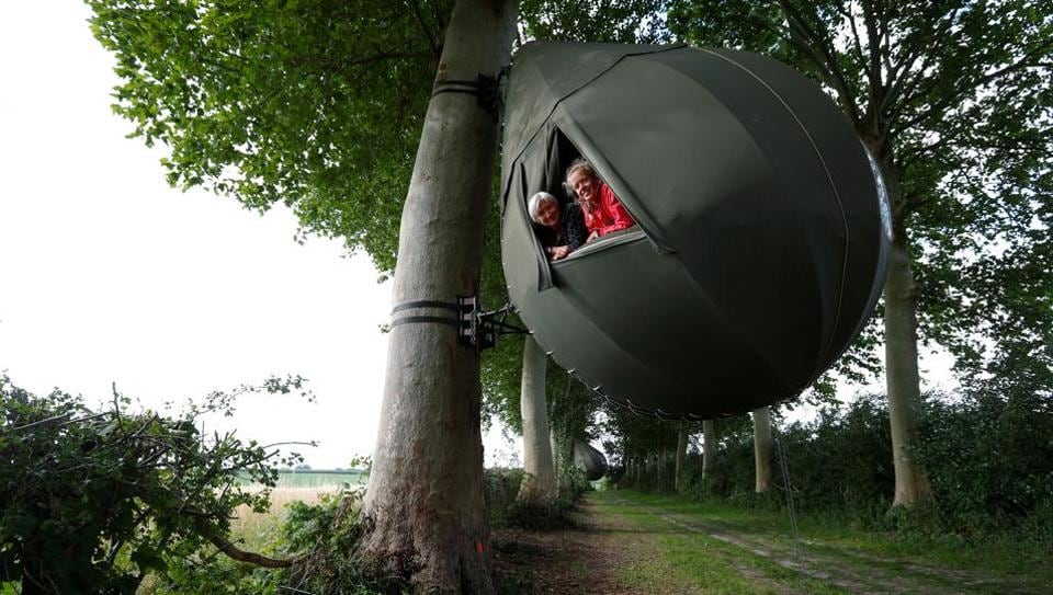 Guests pose a they sit inside a teardrop-shaped tent hanging from a tree created by Dutch artist Dre Wapenaar, offering an unusual accommodation for tourists in the Belgian countryside, near Borgloon, Belgium.  (REUTERS/Francois Lenoir)