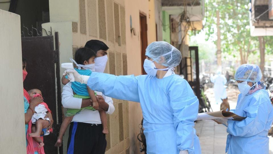 Chandigarh health worker checking people at a sealed area for coronavirus.