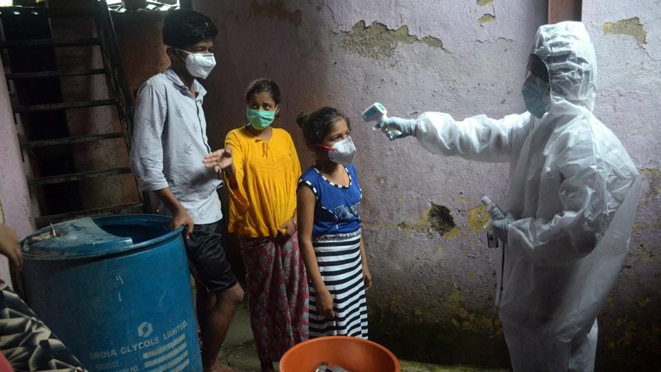 A health worker check temperature of residents of a locality in Navi Mumbai,  Maharashtra,  Wednesday, July 8, 2020.
