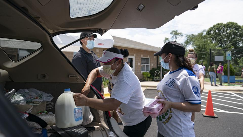 Volunteers place food items in the back of a person's car receiving donations at the Georgetown South Community Center in Manassas, Virginia. On July 7, California, Hawaii, Idaho, Missouri, Montana, Oklahoma and Texas shattered their previous daily record highs for new cases. The biggest jumps occurred in Texas and California, the two largest US states, with more than 10,000 each.  (Alex Edelman / Bloomberg)