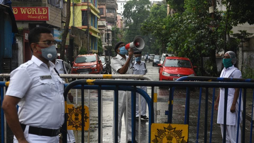 A Kolkata Police personnel uses a  loudspeaker to address residents at Kankurgachi -- one of the new Covid-19 containment zones in Kolkata on Thursday,.