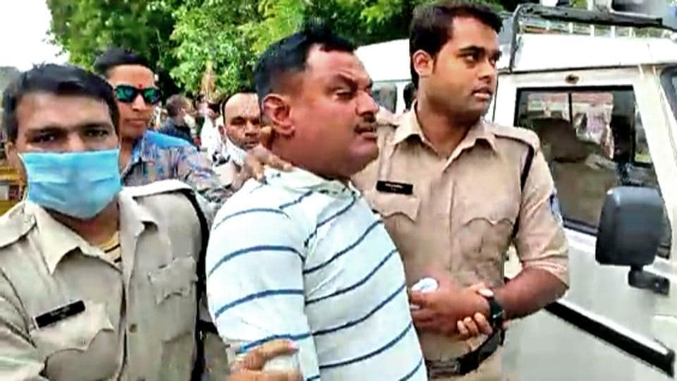 Police personnel arrest Vikas Dubey, the main accused in the Kanpur encounter case, at the Mahakal temple, in Ujjain on Thursday.