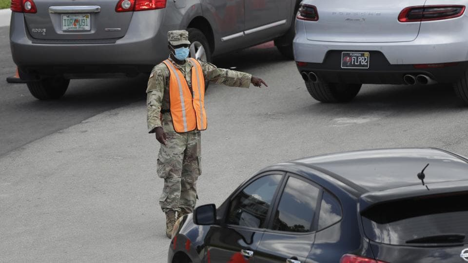A national guardsman directs traffic at a drive-thru COVID-19 testing site outside Hard Rock Stadium in Miami Gardens, Florida on July 8. The United States is undergoing a renewed surge in cases especially in southern and westerns states, with Texas, Florida and California hit the hardest.  (Wilfredo Lee / AP)