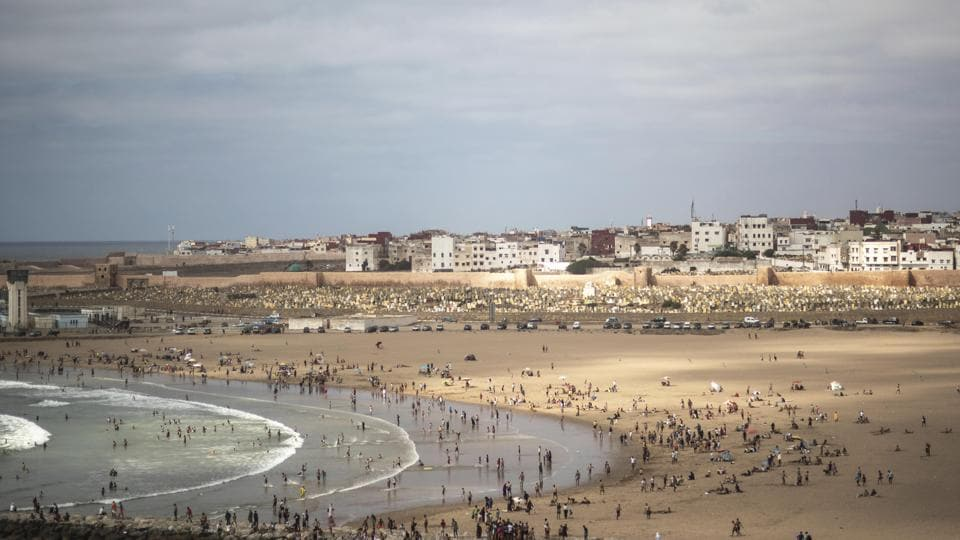 In this Friday, June 26, 2020 file photo, people gather at a reopened beach on the first weekend after lockdown measures were lifted in Sale, Morocco.