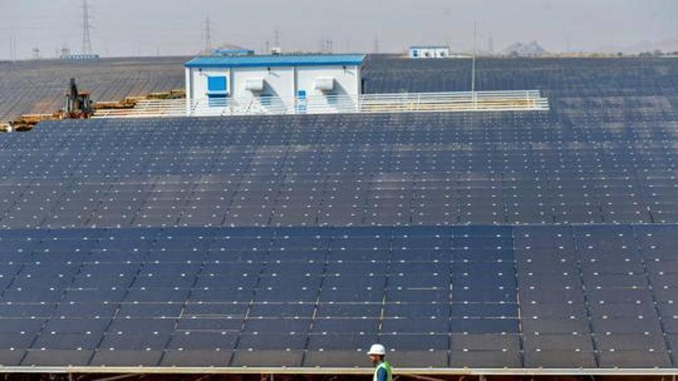 A worker conducts routine checks of solar panels at the newly inaugurated