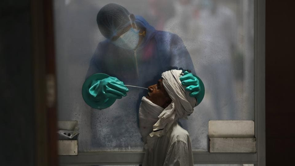 A health worker takes a nasal swab of a person for a Covid-19 test at a hospital in New Delhi. Delhi is placed third among states in terms of number of the coronavirus disease cases.