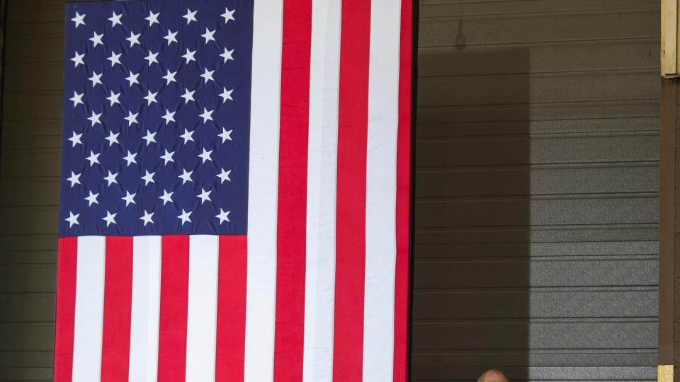 A US Secret Service agent stands at his post beside a large American flag in Dunmore, Pennsylvania.