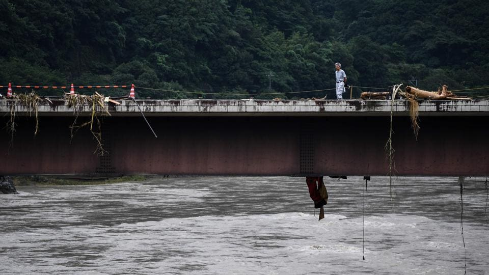 A man walks across a bridge covered with debris in Kuma village on July 9. AFP reported that in many areas, landslides reduced houses to rubble and floodwater rushed into homes in low-lying areas, destroying the contents and rendering them uninhabitable.  (CHARLY TRIBALLEAU / AFP)