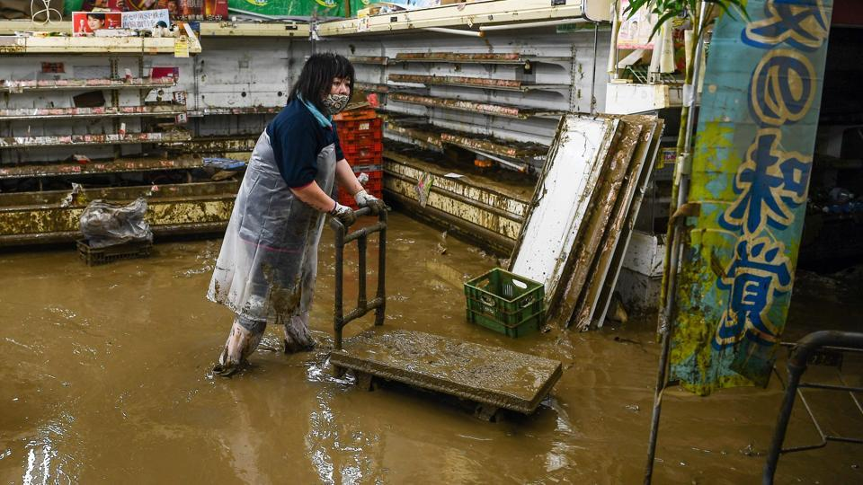 A woman wades in mud water in a supermarket following heavy rains and flooding in Hitoyoshi on July 9. Floodwaters rendered useless all local produce ready to be shipped to customers.  (CHARLY TRIBALLEAU / AFP)