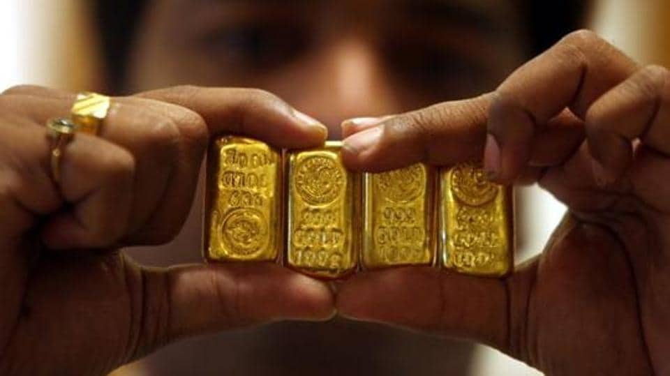 A salesman displays gold bars inside a jewellery shop in Hyderabad.