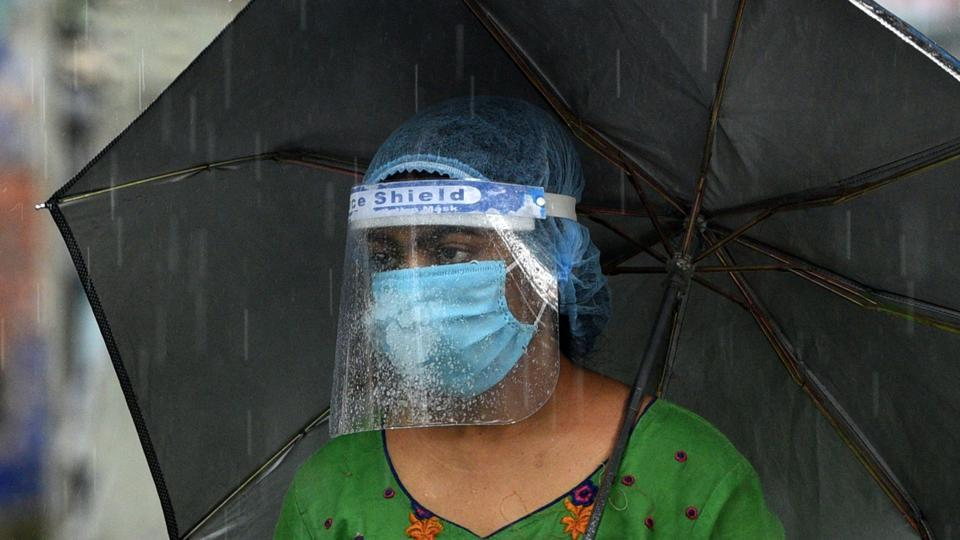 A woman wearing a face shield is seen under an umbrella amid rain in Kankurgachi, Kolkata on July 9.  India's death toll currently stands at 21,604. (Samir Jana / HT Photo)