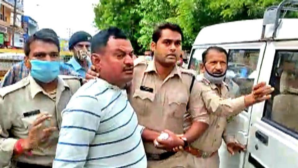 Police personnel arrest Vikas Dubey, the main accused in the Kanpur encounter Case, at the Mahakal temple, in Ujjain. (ANI Photo)