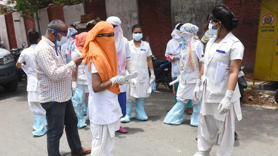 Health workers in protective gear during a large scale screening of residents in the Hindpirhi coronavirus containment zone in Ranchi, Jharkhand.