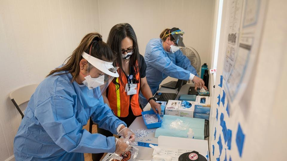 Health care workers wearing personal protective equipment work inside a trailer at a Covid-19 testing site in Concord, California, US.