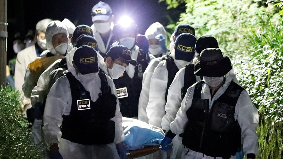 Police officers carry the body of Seoul Mayor Park Won-soon, which was found during a search operation in Seoul, South Korea.