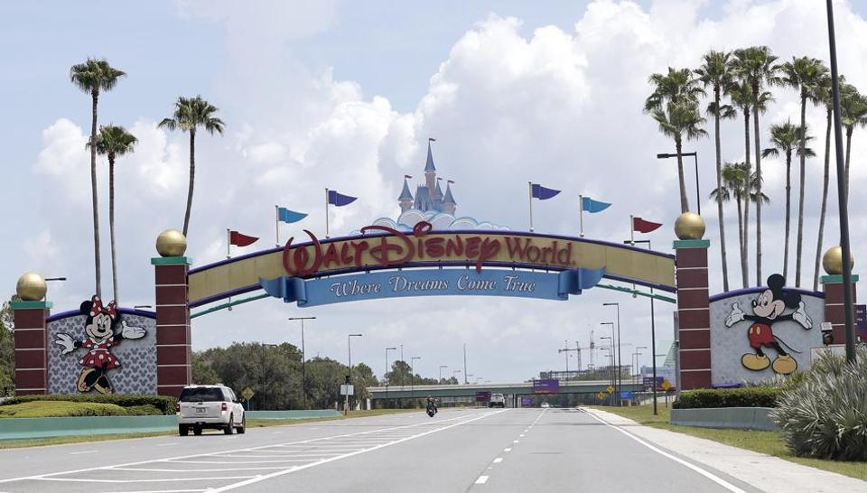 "Cars drive under a sign greeting visitors near the entrance to Walt Disney World, Thursday, July 2, 2020, in Lake Buena Vista, Fla. Despite a huge surge of Floridians testing positive for the new coronavirus in recent weeks, Magic Kingdom and Animal Kingdom, two of Disney World's four parks are reopening Saturday, July 11. When they do, visitors to ""The Most Magical Place on Earth"" will find new rules in place."