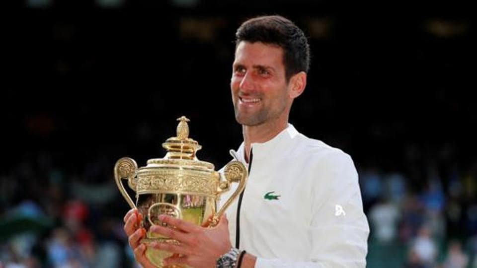 Tennis - Wimbledon - All England Lawn Tennis and Croquet Club, London, Britain - July 14, 2019 Serbia's Novak Djokovic poses with the trophy as he celebrates winning the final against Switzerland's Roger Federer