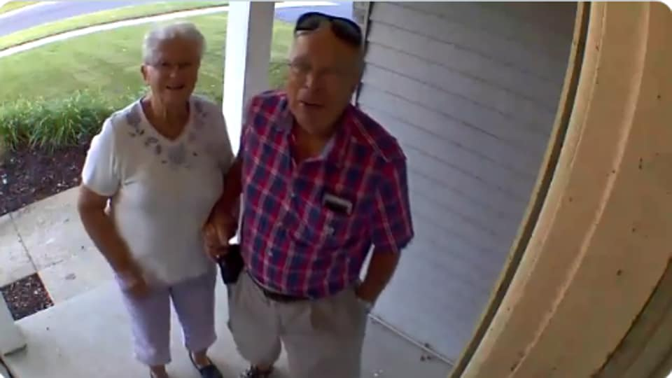 The image shows the grandparents standing in front of their grandson's house.
