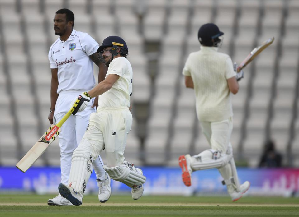 England's Rory Burns, center, and Dom Sibley, right, run past West Indies' bowler Shannon Gabriel to score during the third day of the first cricket Test match between England and West Indies, at the Ageas Bowl in Southampton, England, Friday, July 10, 2020. (Mike Hewitt/Pool via AP) (AP)