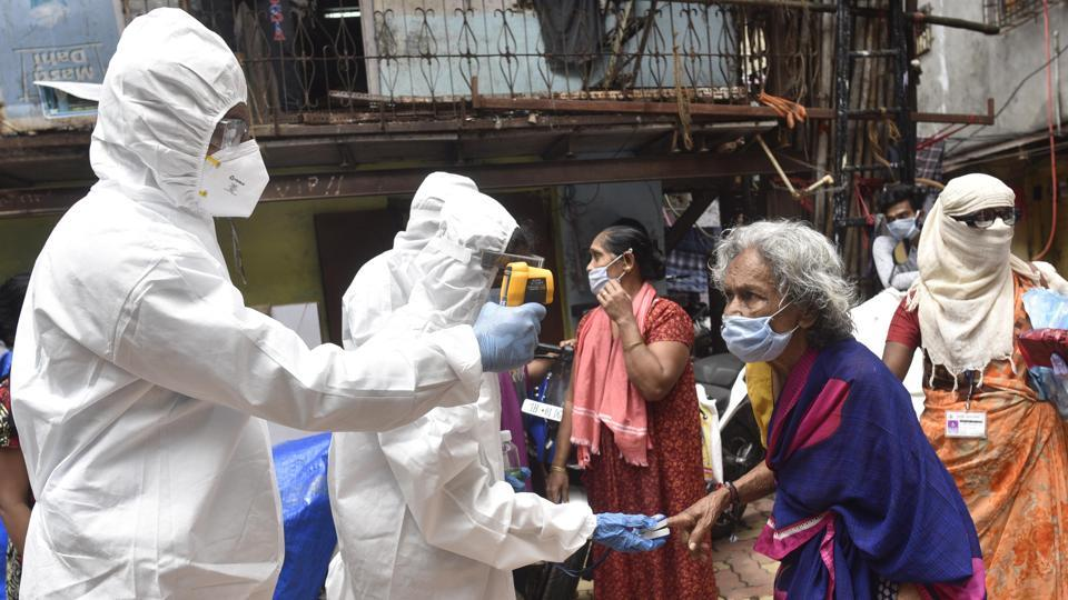 Health care staff check the temperature and pulse rate of the residents of Dharavi during Covid-19 pandemic in Mumbai.
