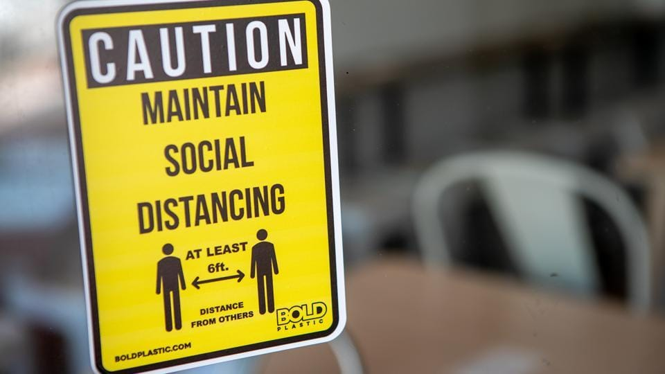 A social distancing sign is displayed in the window of a business. (Representational image)